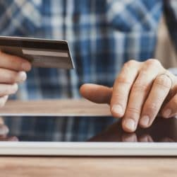 Homme sur tablette numérique avec carte bancaire
