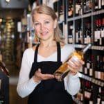 Une vendeuse qui présente une bouteille de vin