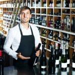 Un vendeur qui présente une bouteille de vin rouge