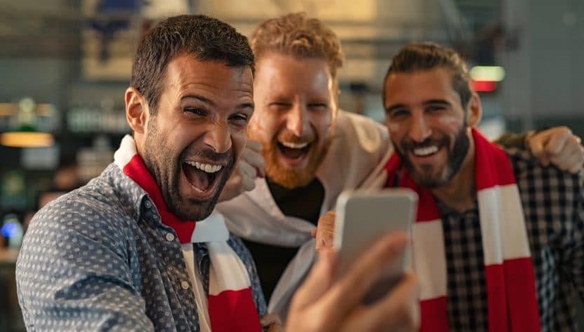 Trois hommes devant un smartphone