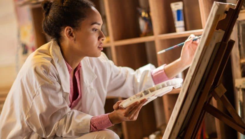 Femme qui peint à l'aide d'un chevalet de peinture