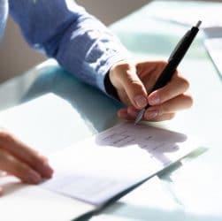 homme signe un chèque