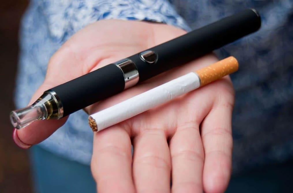 Cigarette et cigarette électronique sur une main