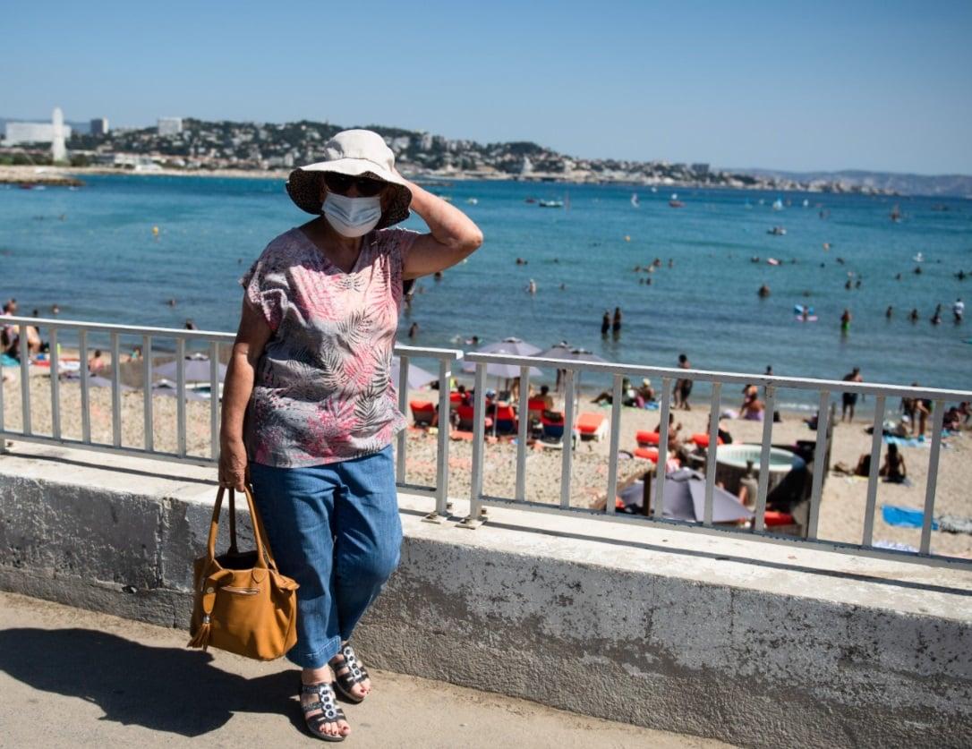Femme qui porte un masque à la plage