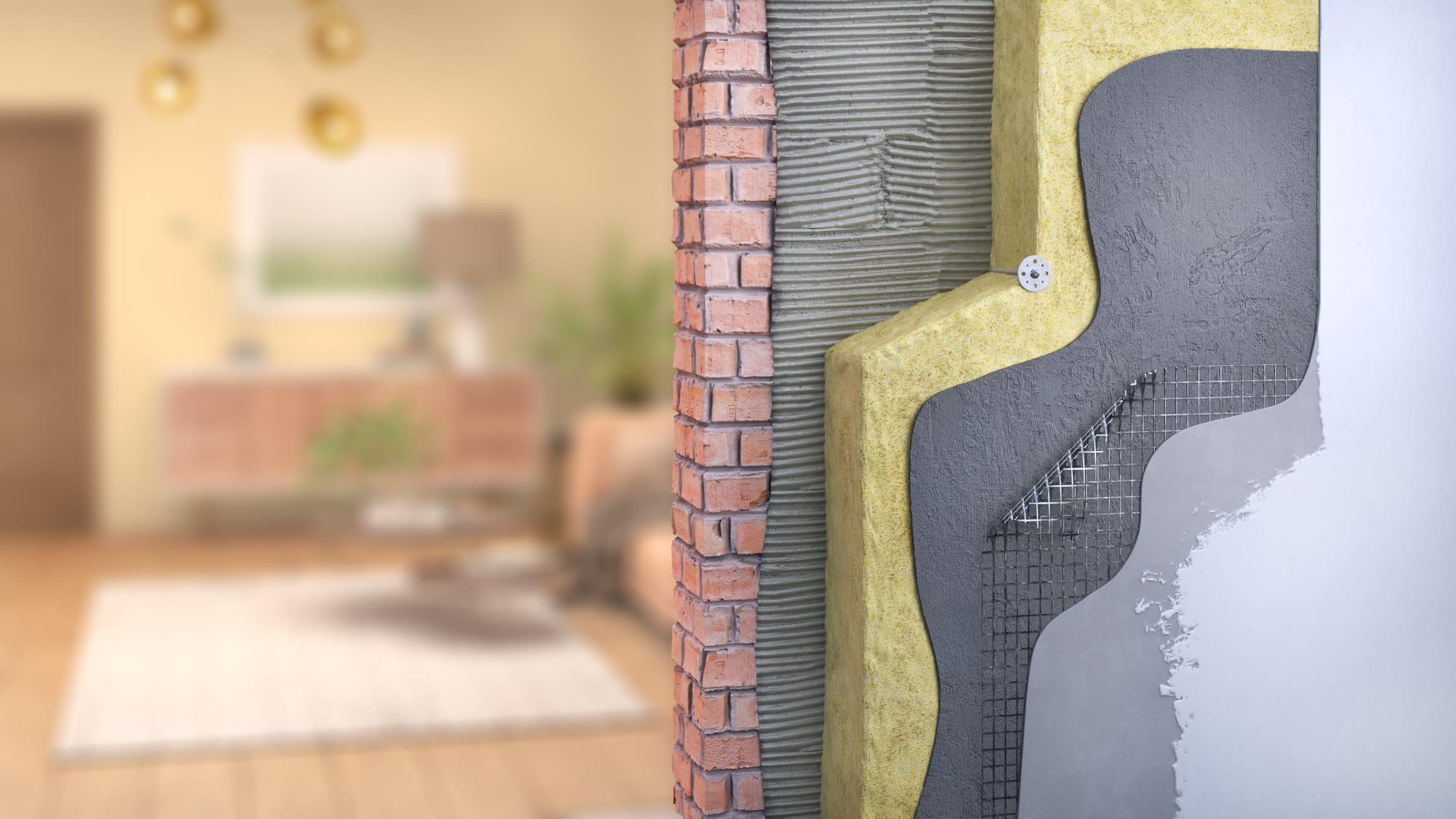 Un homme posant des plaques d'isolations thermiques à l'exterieur