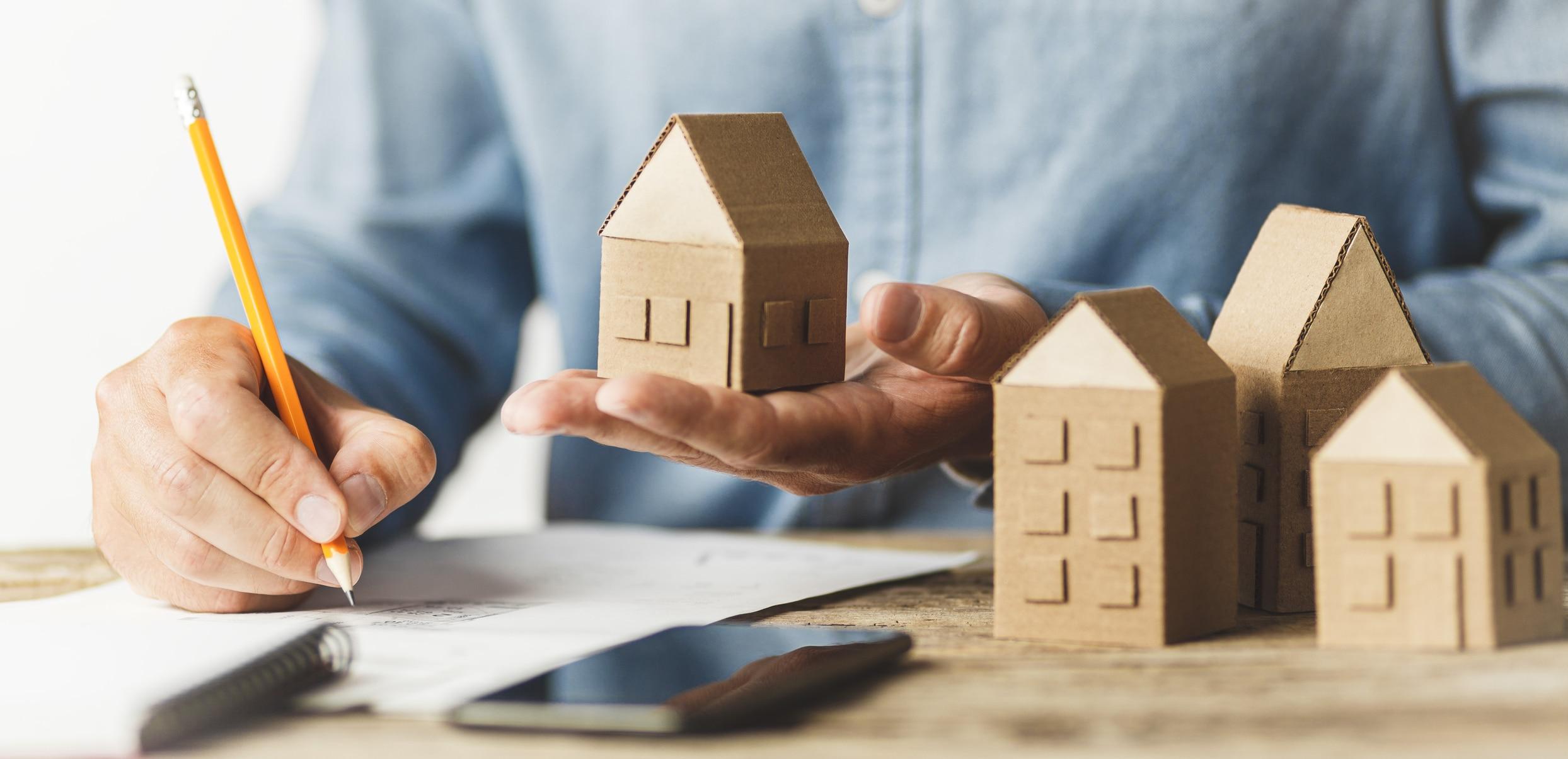 Un homme entrain de calculer avec des petites maisons en cartons dans sa main pour investir