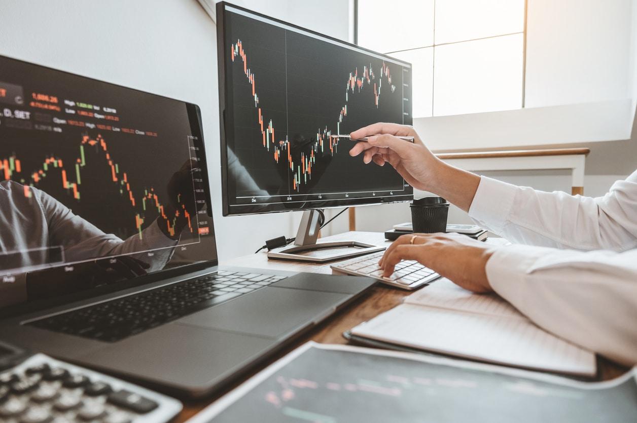 Un homme sur des logiciels de trading sur plusieurs ordinateurs