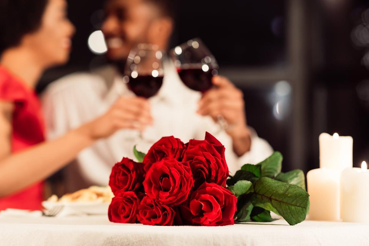 couple diner au restaurant vin rouge fleurs