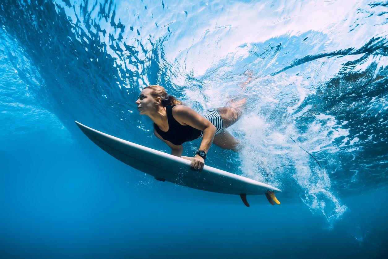 femme avec planche de surf sous l'eau
