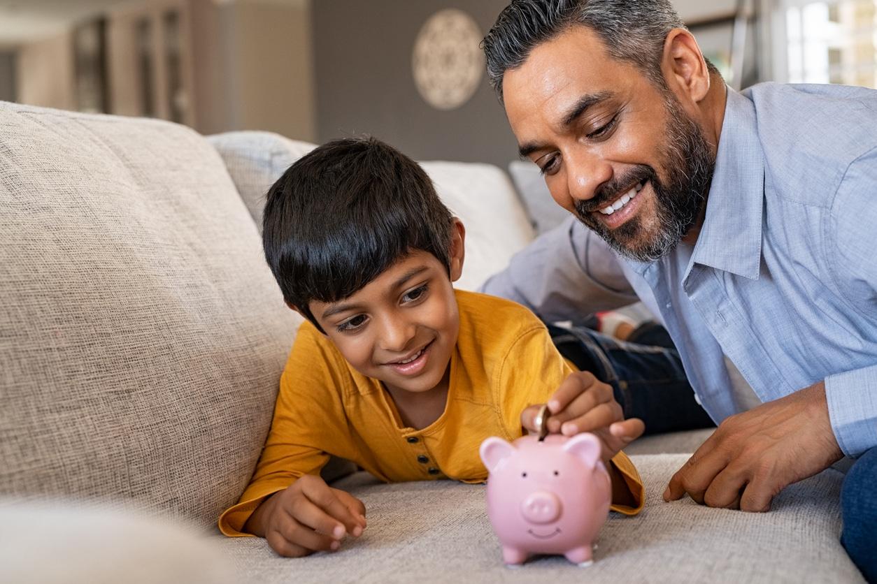 père et fils sur canapé avec une tirelire cochon